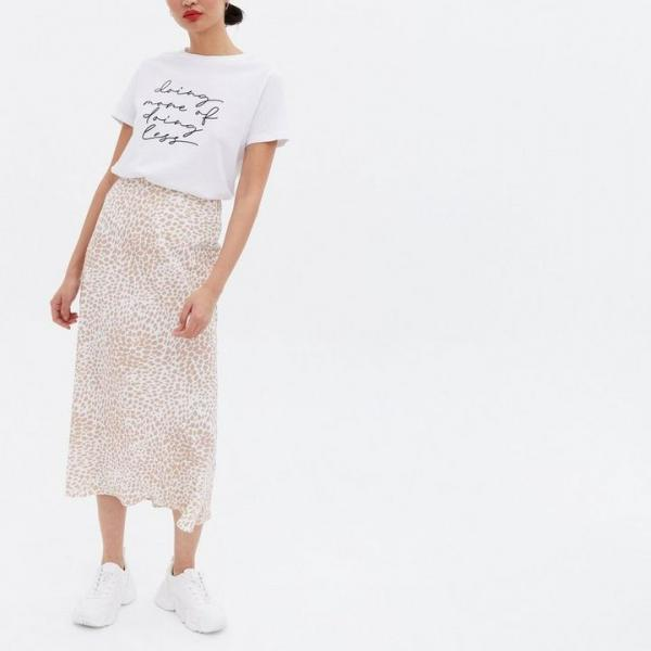 Model wears a mid-length animal print skirt with a white tee - both New Look
