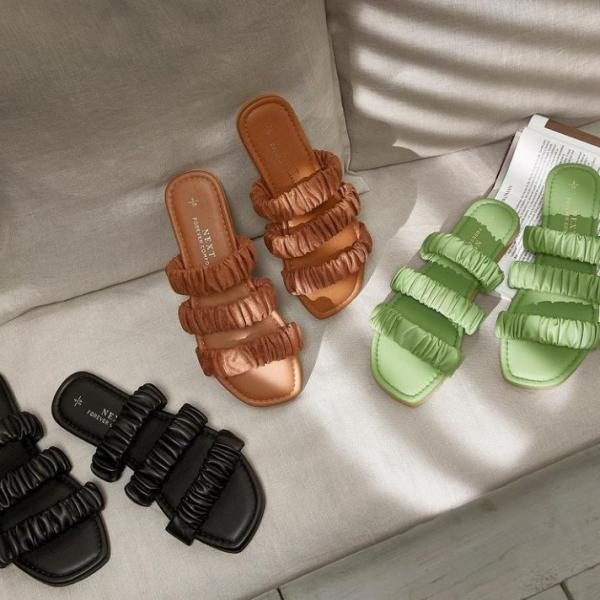 Flatlay of three pairs of flat strappy Next sandals